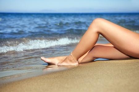 nue plage: belle femme de jambes sur la plage dans l'eau