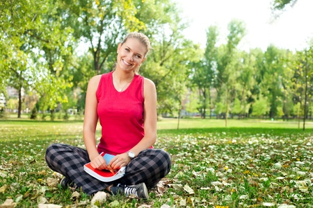 student girl sitting on grass with book in park photo