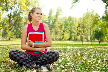 young student girl in park hugging books photo