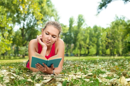 student girl reading book and lying on grass in park  photo