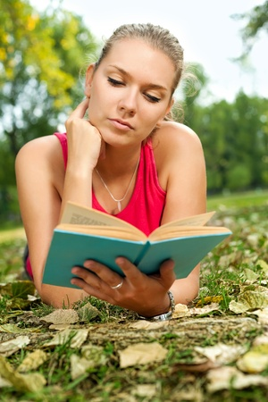 young girl relaxing in park and reading novel photo