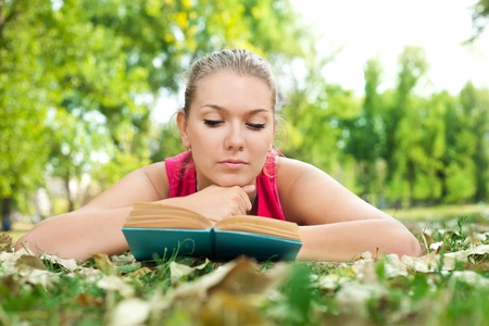 blond girl reading book on grass in park photo