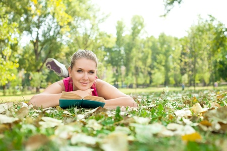 student girl with book lying on grass in park photo