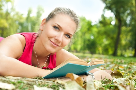 beautiful student reading and relaxing  in park photo