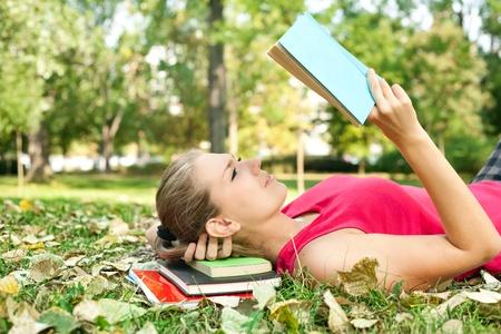 mujer leyendo libro: las mujeres en el Parque concentran en leer el libro Foto de archivo
