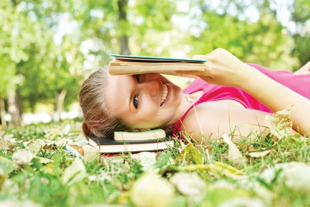 smiling girl reading ridiculous book photo