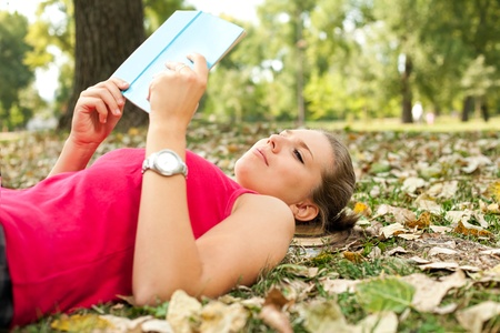 girl lying on leafs in park with book,  relaxing  and enjoying in autumn, photo