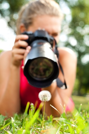 outside shooting: young girl taking picture of  dandelion in nature