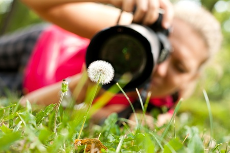 outside shooting: female  photograph with camera taking a picture of flower