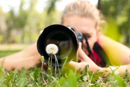 outside shooting: photographer - girl making pictures of flower in nature Stock Photo