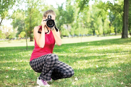 photographing: beautiful young woman with camera on nature