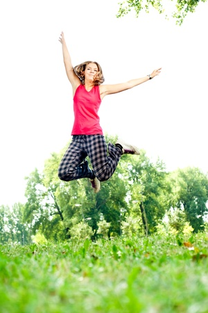 vertical wellness: beautiful young girl  jumping in the park