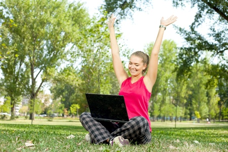 happy,  beautiful woman with laptop on nature photo