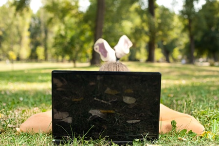 laptop outside: Young woman lying on grass in park behind laptop