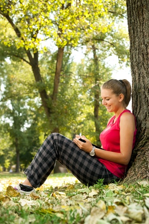 student girl sitting in park and writing in notebooks photo