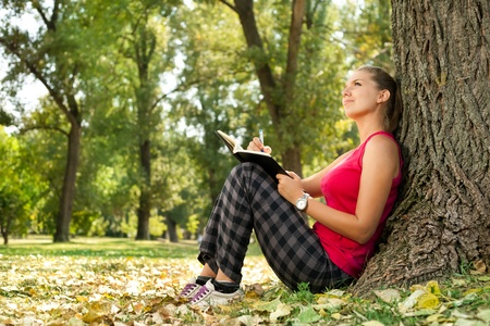 young woman writing in park Stock Photo