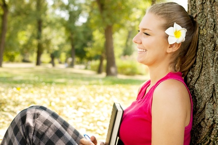 studding: smiling student girl sitting in park next tree Stock Photo