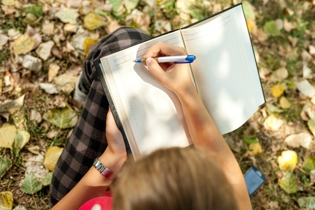 girl sitting outdoor and writing , top view Imagens
