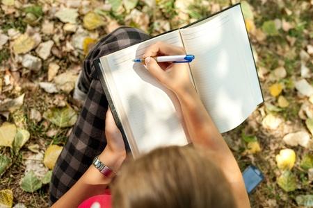 meisje zitten buiten en schrijven, bovenaanzicht Stockfoto