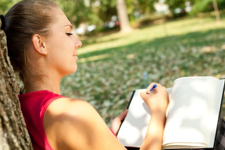 note book:  young girl writer in park, writing book
