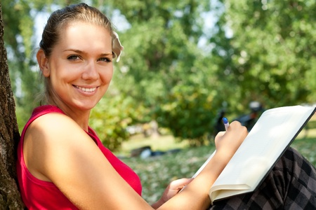 smiling girl sitting and writing in notebook outdoor photo