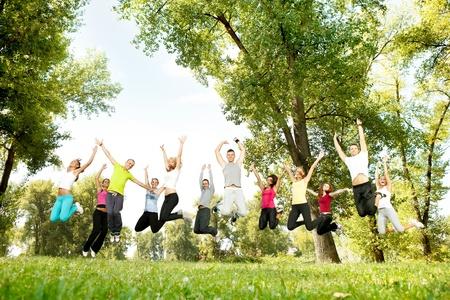 springende mensen: grote groep jonge studenten springen mensen met handen omhoog