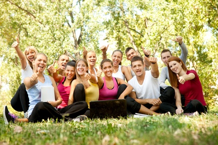 happy students with laptop in park showing sign ok thumb Stock Photo