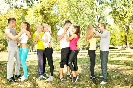 group of young people dancing in park, four couple having fun photo