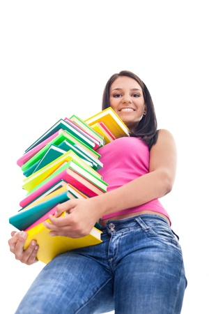 smiling girl holding big stack of color books and looking down, isolated on white background photo