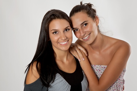 young sisters hugging on gray background, two smiling girls Stock Photo - 10687101