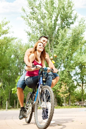laughing couple on a bike in the park  photo