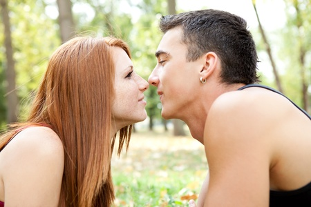 couple kissing on romantic date in park photo