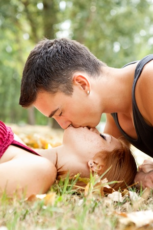 young man kissing his girlfriend in park  photo