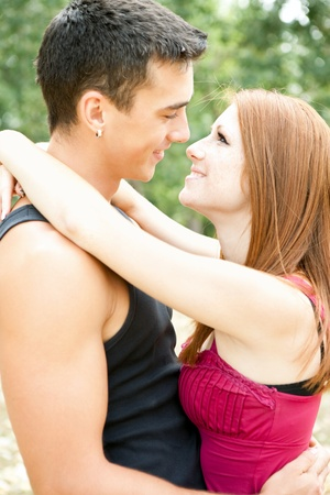 portrait of happy embracing couple in park photo
