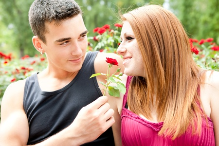 young romantic couple,  red flowers in background photo