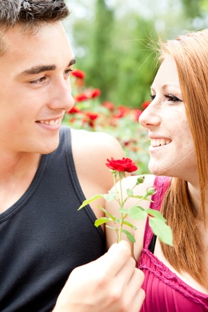 boyfriend giving red flower her girlfriend, smiling young couple photo