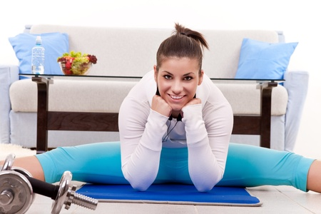 young woman stretching on floor at home  photo