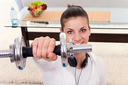 girl holding weights have training at home   photo