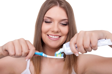 young woman putting  paste on toothbrush, isolated on white background photo