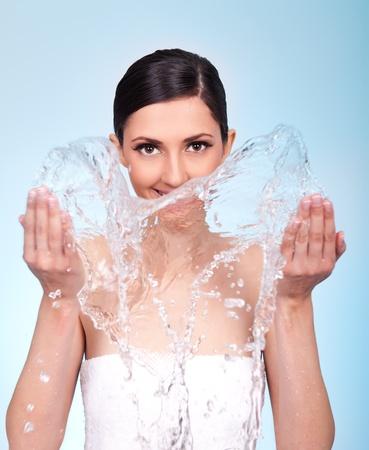 caucasian water drops: woman washing her face with clan water, studio shot