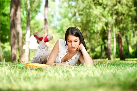 field study:  student girl relaxing and reading book in park, school education