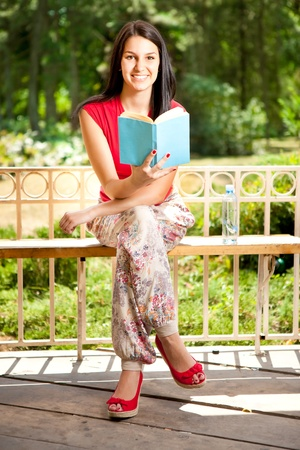 smiling girl with book in park, sitting on bench photo