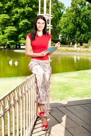 beautiful teenager girl with book in front lake photo