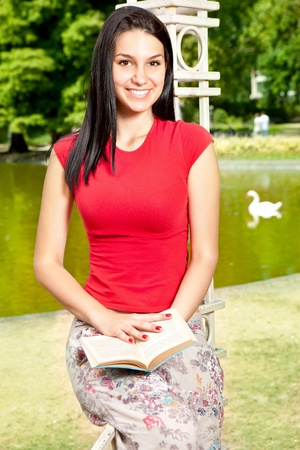 smiling girl reading outdoor in front lake in park photo