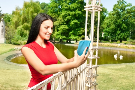 teenager girl with book in park in front lake photo