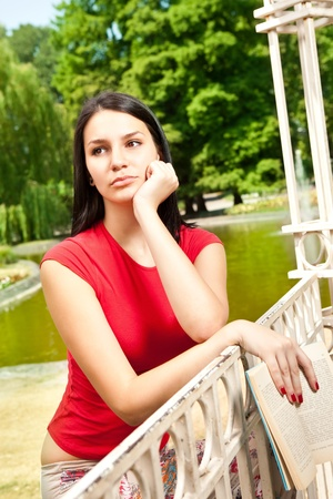 thinking young girl in park in front lake photo