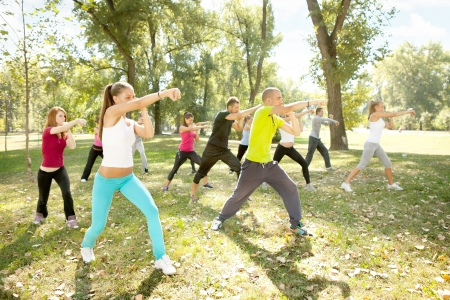man outdoors: large group of young people training kickboxing, outdoor