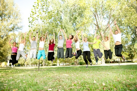 spring time:  group of young people jumping  with hands up, outdoor Stock Photo