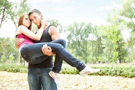 baiser amoureux: homme tenant une belle jeune fille en les regardant caméra Banque d'images
