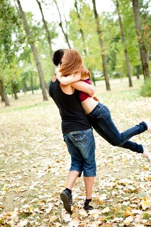 women hugging: young couple having fun in park